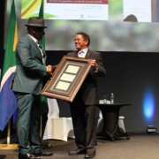 Deputy Minister of Agriculture, Forestry and Fisheries, General Bheki Cele, hands over a gift to WFC Secretary General, Trevor Abrahams, at the closing ceremony, to thank him for a job well done.